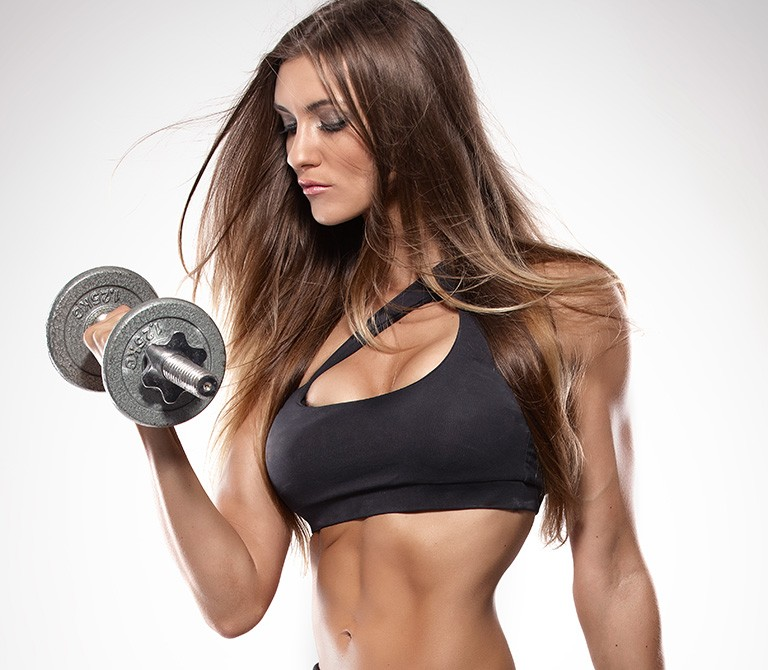 Nice sexy woman doing workout with dumbbells isolated over white background